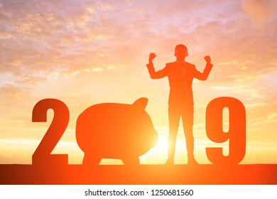 silhouette of business man feel excited with 2019 and piggy bank