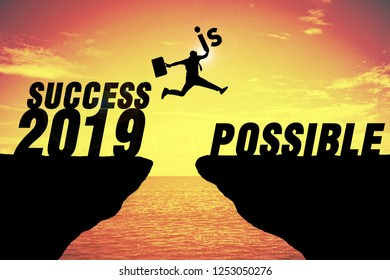 Silhouette of business man jump between cliff. keep go on to success concept at 2019 success possible over a beautiful high view sunrise sea background. Success in 2019 years. GO TO 2019 YEAR CONCEPT