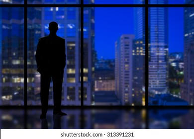 Silhouette of a Business Man looking out of high rise office window at night