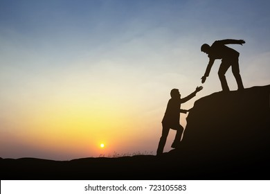 Silhouette of business man on mountain and sunset background. Business teamwork success concept.