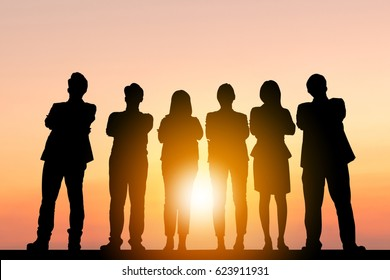 Silhouette of Business People Celebration Success Happiness Team standing with arms crossed at Sunset Evening Sky Background