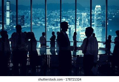 Silhouette of Business People Discussing with City Lights