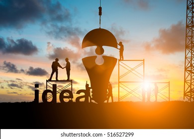 Silhouette Business people shaking hands and Team business engineer work connecting jigsaw puzzle piece together. idea of progress over blurred natural.Teamwork potential and motivate growth concept