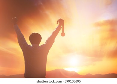 Silhouette business people victory raising hands and holding gold medal with sunset sky. Motivation and success concept.