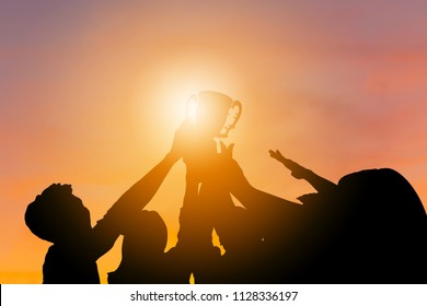 Silhouette of Business team with clipping path holding award trophy show their victory when business success sunset background
