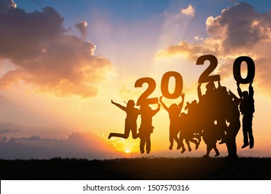 Silhouette of Business teamwork hands up and jump to the beautiful golden sky from text 2020 background .The concept of business sucess,victory,achieve target goal,busness growth.