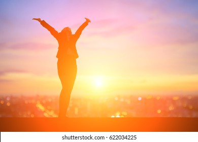 silhouette of business woman feel free with sunset