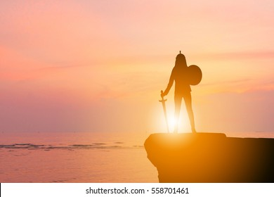 Silhouette of Business woman Knight Sword and Shield in Sunset Background, Fighting Business Warrior Concept.