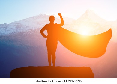 silhouette of a business woman superhero with a cloak standing on top of a mountain in a pose of success in the sunlight