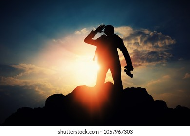 silhouette of businessman with binocular for searching a opportunity on top of mountain against sun light