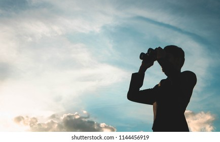 Silhouette of Businessman with binoculars to look for opportunities for success.