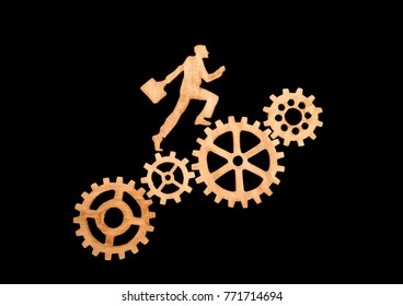 silhouette of a businessman with a briefcase going to success through gear set. Career growth, promotion, and teamwork. Of natural wood black background.
