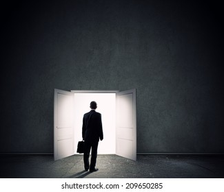 Silhouette of businessman with briefcase standing in doorway