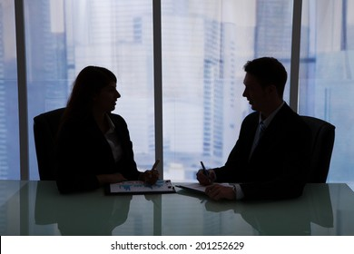 Silhouette businessman and businesswoman discussing at desk in office