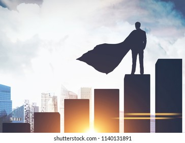 Silhouette of a businessman in a cape standing on a giant bar chart and looking at a modern cityscape. Toned image double exposure mock up