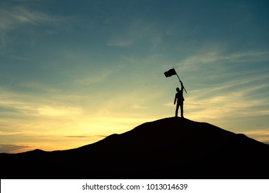 Silhouette of businessman celebrating success on top of hill, sky and sun light background.  Vintage filter. Business, success, leadership, achievement, teamwork and people concept.