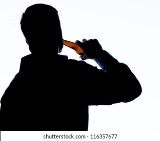 Silhouette of a businessman drinking alone. Isolated on white, Blue cold glow on the silhouette. Digitally altered image.