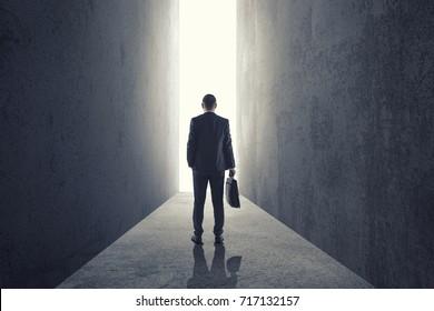 Silhouette of businessman entering giant doorway