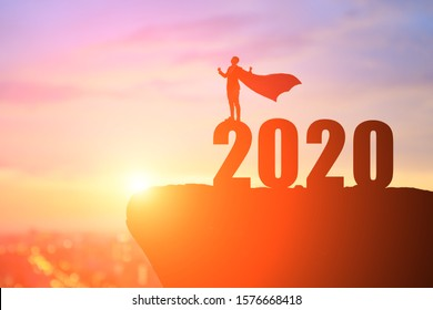 silhouette of businessman feel excited with 2020 on the mountain