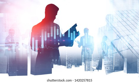 Silhouette of businessman with folder and members of his team over cityscape background with double exposure of graphs. Stock market concept. Toned image