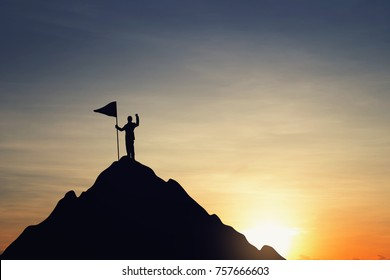 Silhouette of businessman hold a flag on top mountain, sky and sun light background. Vintage filter. Business, success, leadership, achievement and people concept.