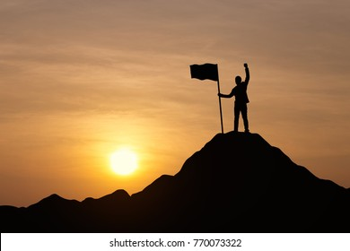 Silhouette of businessman holding a flag on top mountain, sky and sun light background. Vintage filter. Business, success, leadership, achievement and goal concept.