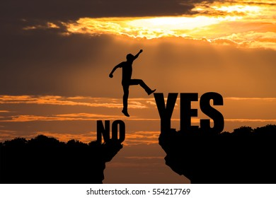 Silhouette of businessman jumping from NO to YES on sunrise background. business concept