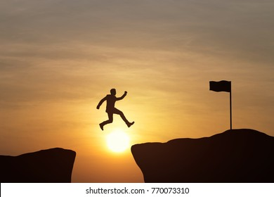Silhouette of businessman jumping on top mountain at sky and sunset background. Business success concept. Vintage filter.