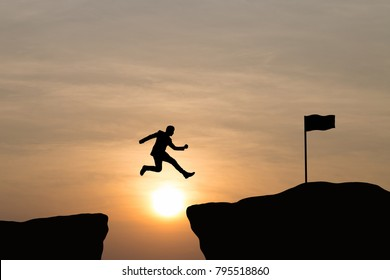 Silhouette of businessman jumping on top mountain, sky and sunset background. Vintage filter. Business, success, leadership, achievement and goal concept.