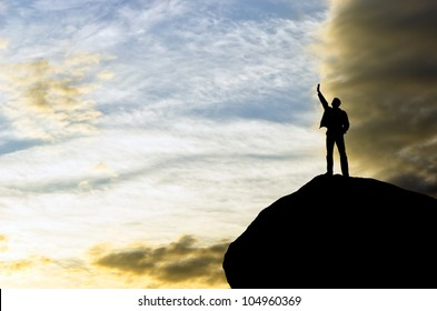 silhouette of a businessman with a laptop in hand is on top of a mountain in the sky with clouds.
