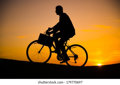 Silhouette of Businessman Riding Bicycle Up a Hill