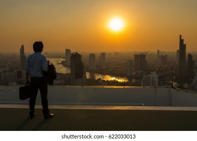 Silhouette of businessman standing with carrying the business bag and looking the vision over the cityscape background at sunset time with lens flare,Business success concept