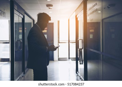 Silhouette of businessman use phone,Sad and Serious Man chatting alone infront of closeing office.Dramatic moment.Split tone instagram like.With hot light Processed.