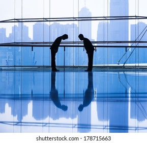 Silhouette of Businessmen Bowing by City Skyline