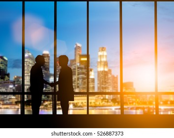Silhouette businessmen shake hands finishing a deal between businesses over blurred employees the city night Success of the joint venture business growth and progress and potential concepts.