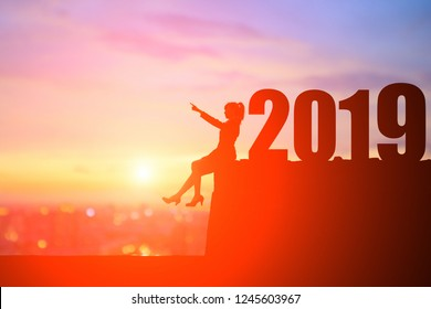 silhouette of businesswoman pointing something and sit on the cliff with 2019