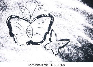 The silhouette of the butterfly painted with white flour on a dark background.