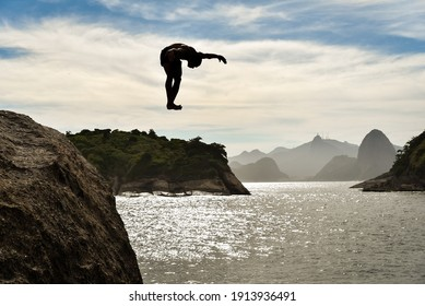 Silhouette of a Buy Jumping Into the Ocean With Sugarloaf Mountain and Corcovado on Background, in Niteroi, Rio de Janeiro, Brazil