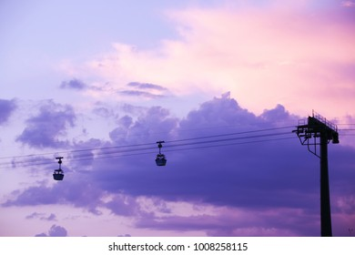 Silhouette of a cable car over ultraviolet cloudy sky. Cabins on the railway