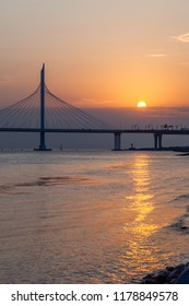 Silhouette of a cable-stayed bridge on a background of a red orange sunset. St. Petersburg.