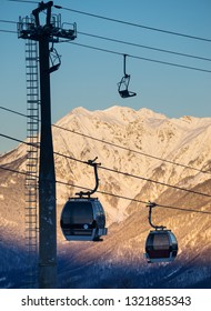Silhouette of cableway in motion on rise and descent on background beautiful landscape of snowy high mountains Caucasus on the winter resort of Krasnaya Polyana