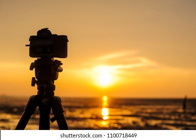 Silhouette of a camera or DSLR on a tripod with golden sunset at the beach background.