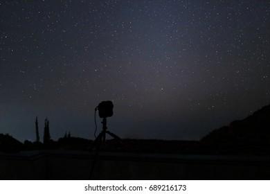 Silhouette camera on tripod with beautiful stars on night sky background.