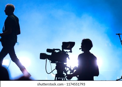 Silhouette of a cameraman and a guitarist in a concert. Blue atmosphere. Live Concert