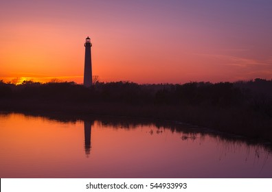 Silhouette of Cape May Lighthouse reflecting in the water