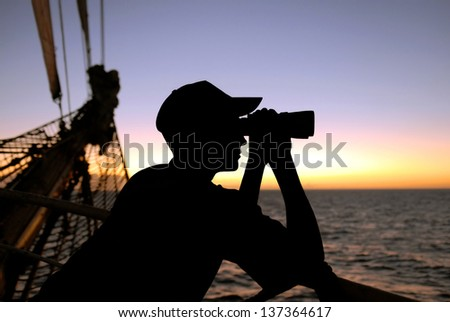 silhouette captain looking through binoculars