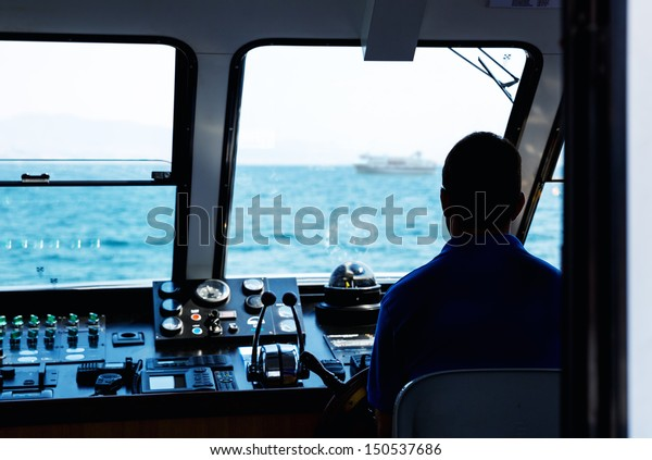 Silhouette of captain steering boat