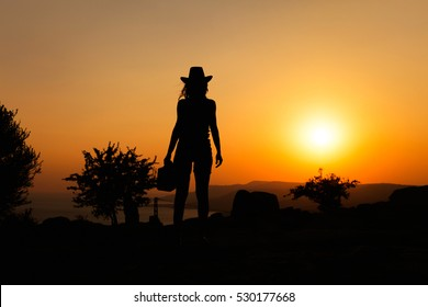 Silhouette capture of a woman with cowboy hat on hill at sunset