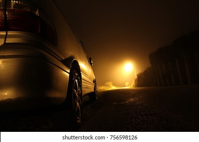 The silhouette of a car, standing on the side of the road on a misty night. The glare of the street light against the fog sets a creepy mood. Concept of thieves, rapist and killers roaming in the dark