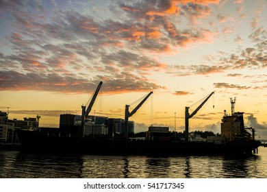 Silhouette of the cargo ship over the beautiful sunrise and amazing sky clouds in Labuan Pearl of Borneo,Malaysia.